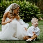 Bride holding a drink while sitting next to young boy