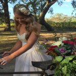 Bride outdoors with curled hair with a flower accessory on it next to a bike with flowers