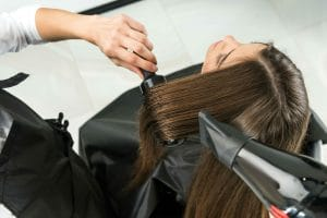 Woman getting her hair blow dried at salon